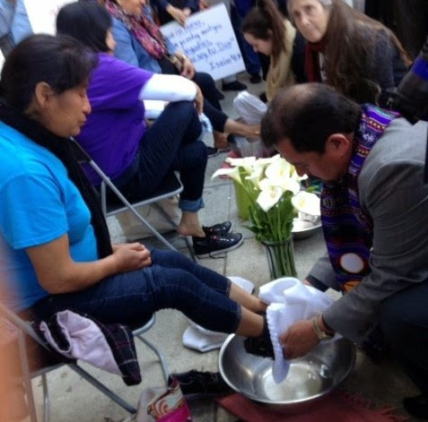 Pastor Pablo Morataya washes the feet of a woman who fled violence in h er country. She is in deportation proceedings seeking protection and currently must wear a GPS ankle monitoring device.