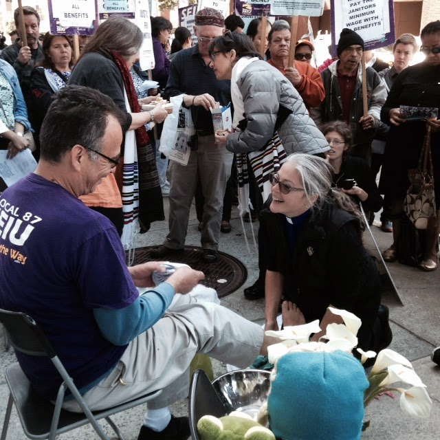 """Rev. Stephanie Etzbach-Dale washes the feet of a member of SEIU. """"Footwashing is a sacrament of love which tears down the barriers of privilege, hierarchy and separation- and uniting us.""""- Rev. Maria Eitz, Sophia Trinity"""